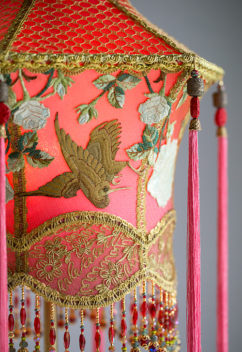 Detail of 1920s antique floor lamp with scrolls has been hand painted and holds a hand-dyed exotic Chinoiserie Red Lantern with Cranes silk lampshade.
