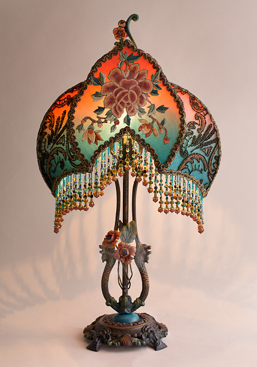 The shade is covered with antique textiles including antique metallic lpatterned ace and ornately beaded 1920s flapper dress remnants. The front panel features a finely embroidered antique Chinese Peony applique and the surrounding trim is inset with wonderful multicolored beaded passimenterie while the sides of the shade are covered with colorful floral net trim.